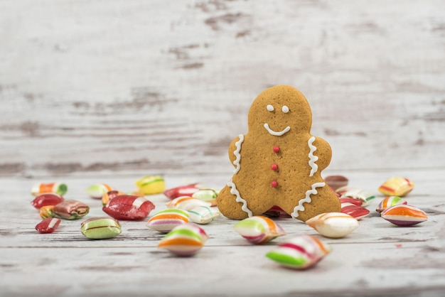 Close de doces coloridos e bonecos de gengibre em uma superfície de madeira branca