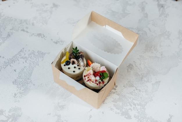 Close de dois bolos de bagatela lindos e deliciosos sobre uma superfície clara em uma caixa de presente. sobremesa, comida saudável.