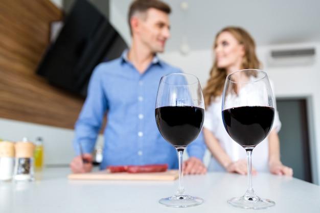 Close de dois copos de vinho tinto e casal feliz em pé na cozinha Foto Premium