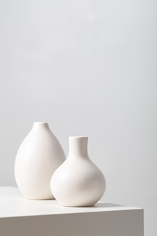 Close de dois vasos de barro branco na mesa sob as luzes no branco