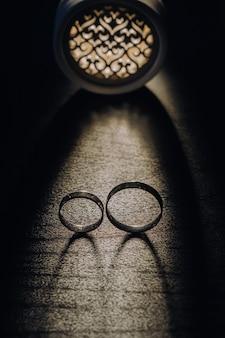 Close de duas alianças de ouro em um fundo preto