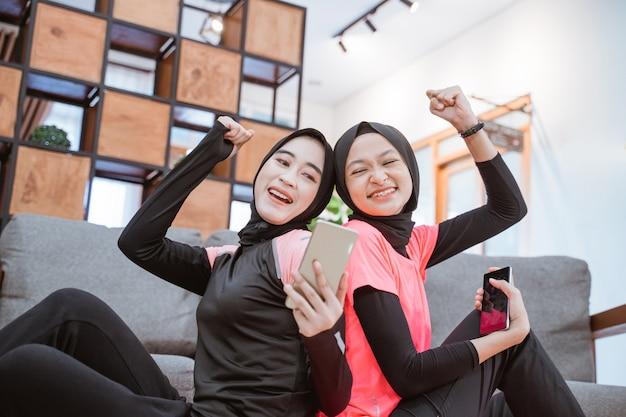 Close de duas garotas vestindo roupas esportivas hijab que ficam felizes em serem surpreendidas ao ver a tela de um celular enquanto estão sentadas no chão da casa