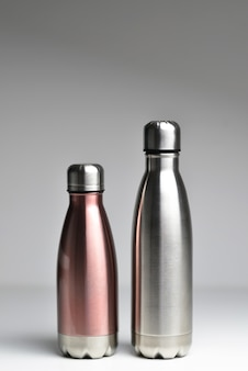 Close de duas garrafas de água térmicas de aço reutilizáveis isoladas em um fundo cinza com espaço de cópia