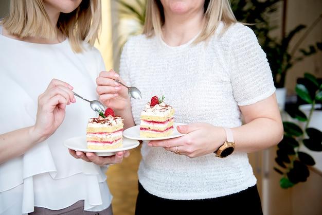 Close de duas mãos de mulheres comendo bolo de creme decorado com frutas vermelhas