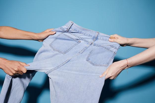 Close de duas mulheres puxando o último jeans à venda em direções diferentes contra o fundo azul