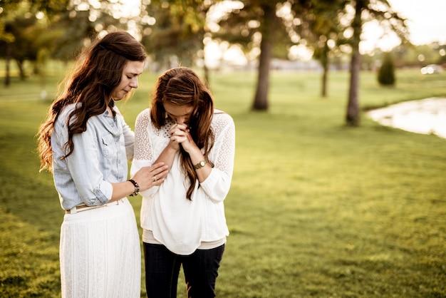 Close de duas mulheres rezando