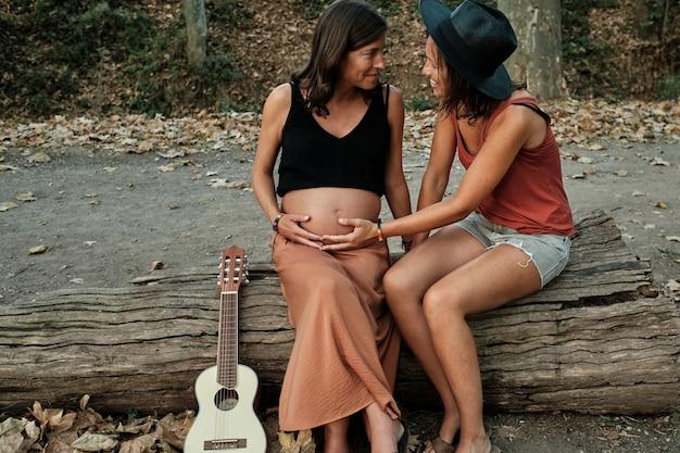 Close de duas mulheres segurando a barriguinha do bebê em um parque e um ukulele