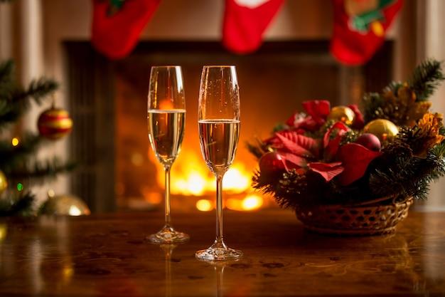 Close de duas taças de champanhe em frente à lareira acesa