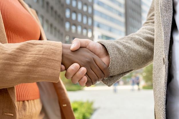 Close de empresários apertando as mãos e se cumprimentando ao ar livre