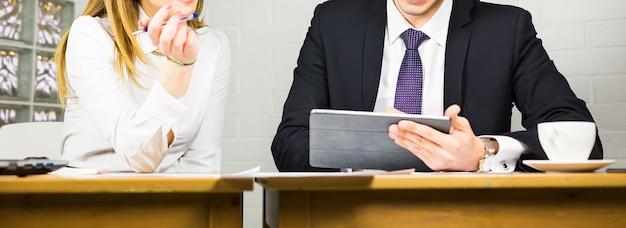 Close de empresários com tablet digital sentados em um escritório moderno