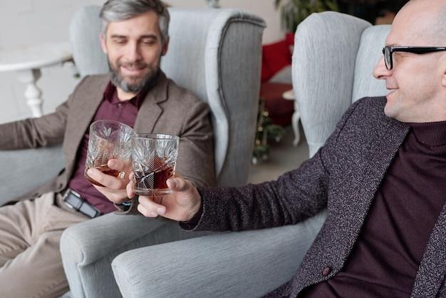 Close de empresários de meia-idade sentados em poltronas confortáveis e copos de uísque tilintando enquanto celebram novo contrato