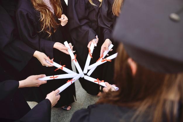 Close de estudantes de graduação em vestes pretas ou manto segurando diplomas ou certificados de graduação de uma instituição de ensino superior.
