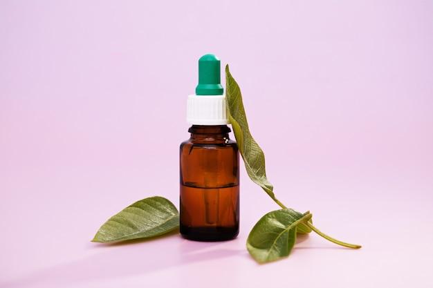 Close de extratos de folhas medicinais em um frasco de remédio sobre um fundo rosa
