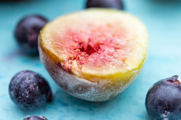 Close de figos deliciosos congelados e amoras silvestres isoladas em um azul