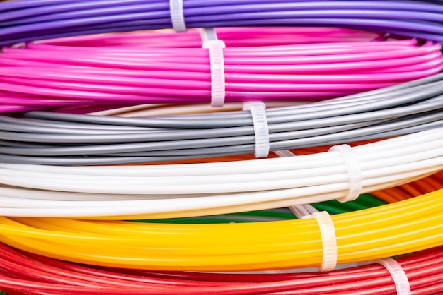 Close de fios brilhantes de plástico para impressora 3d dentro de casa