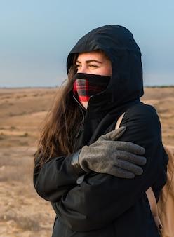 Close de foco raso vertical de uma mulher se abraçando por causa do frio