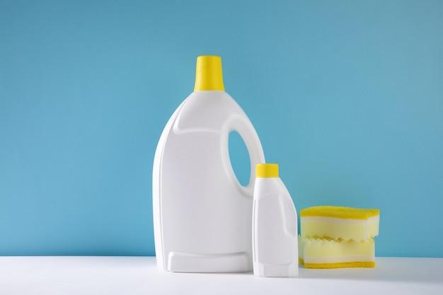Close de foco seletivo de galões de detergente de limpeza e esponjas em uma parede azul