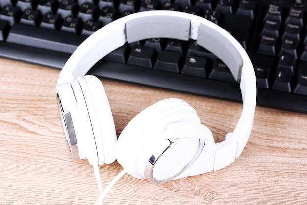 Close de fone de ouvido e teclado em uma mesa de madeira