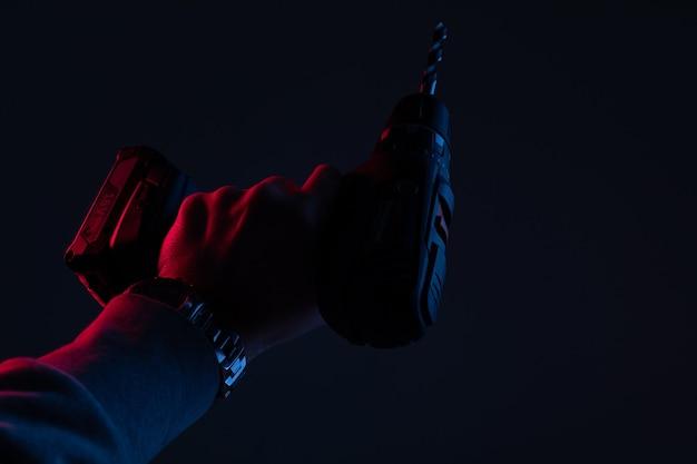 Close de furadeira elétrica em luz de néon em uma parede preta