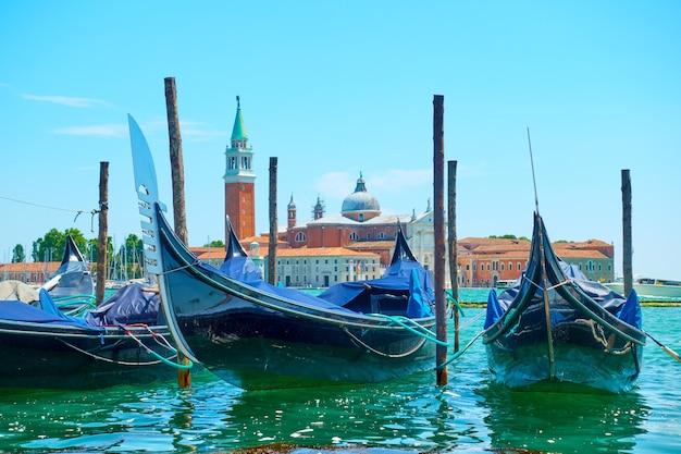 Close de gôndolas atracadas e a igreja de san giorgio di maggiore em veneza, itália Foto Premium