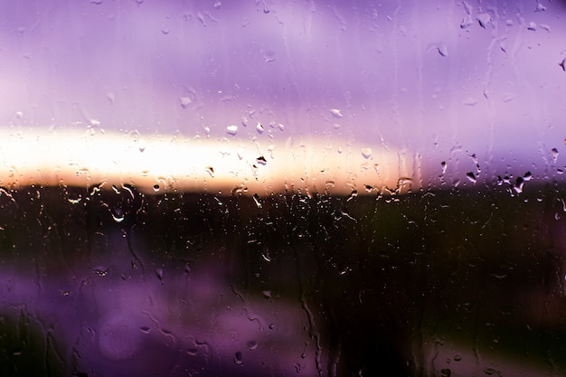 Close de gotas de chuva na superfície roxa da janela