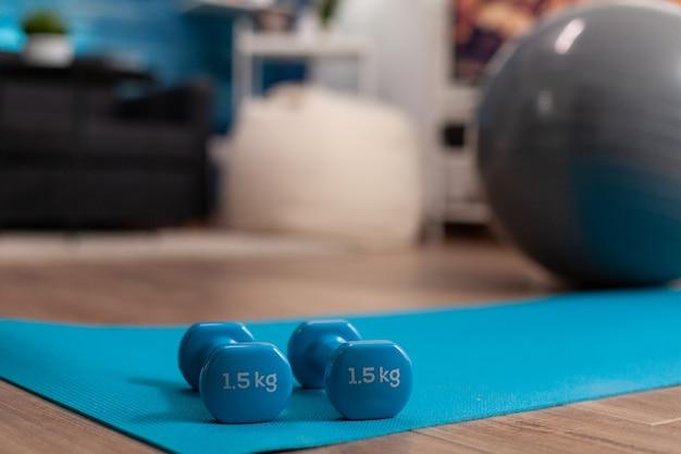 Close de halteres de fitness em pé no tapete de ioga na sala de estar sem ninguém pronto para o treino de pilates, trabalhando com exercícios de saúde corporal