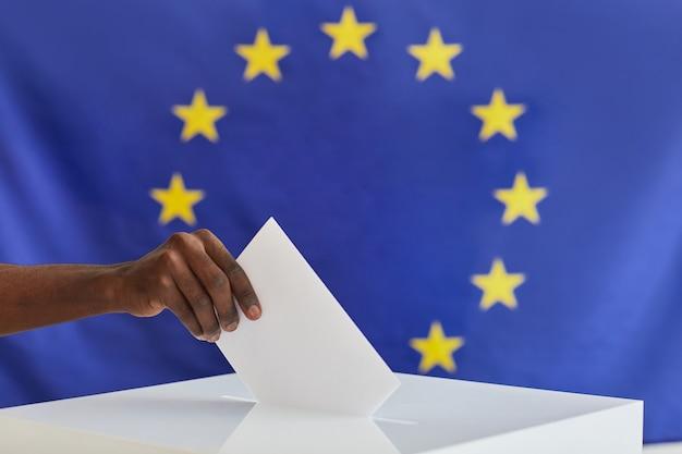 Close de homem africano colocando o envelope na caixa durante a votação