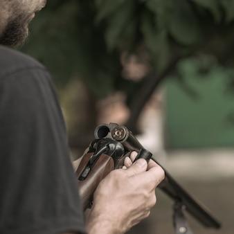Close de homem carregando rifle de caça de cano duplo