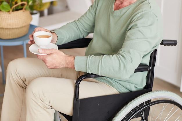 Close de homem com deficiência sentado em uma cadeira de rodas com uma xícara de chá em casa