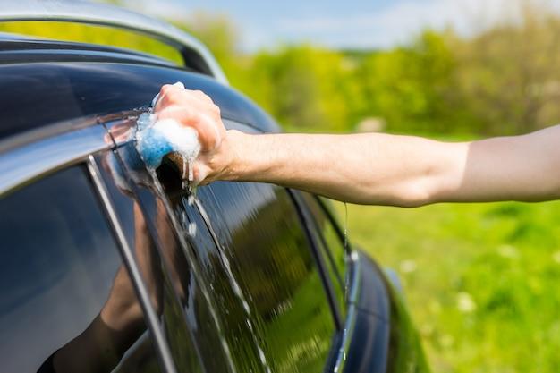 Close de homem lavando janelas de veículo de luxo preto com esponja com sabão em campo verde em dia de sol