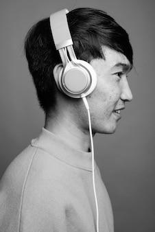 Close de jovem asiático ouvindo música
