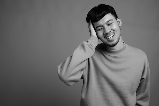 Close de jovem asiático vestindo suéter