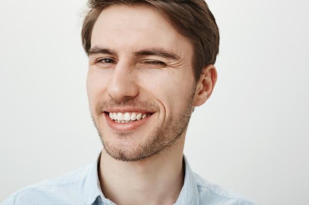 Close de jovem bonito com dentes brancos sorrindo satisfeito, piscando atrevido