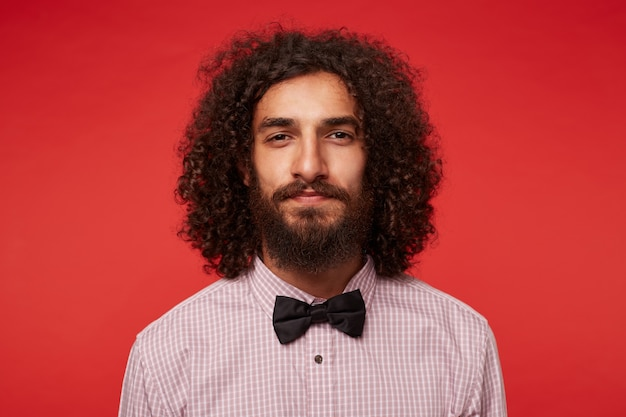 Close de jovem charmoso moreno cacheado com barba exuberante olhando para a câmera com os lábios dobrados, vestindo roupas elegantes em pé contra um fundo vermelho