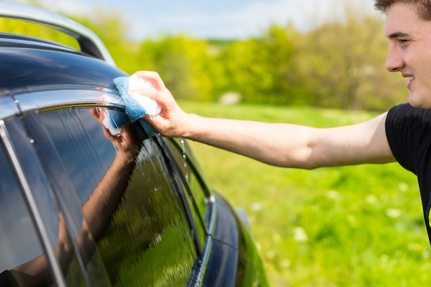 Close de jovem lavando janelas de veículo de luxo preto com esponja com sabão em campo verde em dia de sol