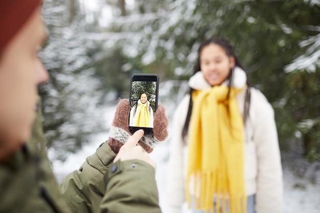 Close de jovem segurando um telefone celular e fotografando a mulher que posava contra as árvores nevadas da floresta