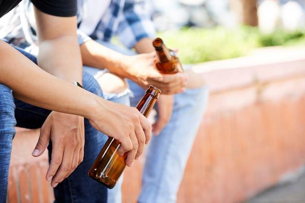 Close de jovens segurando garrafas de cerveja, sentados ao ar livre