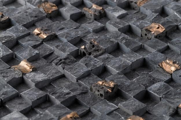 Close de ladrilhos quadrados pretos antigos de uma parede sob as luzes - legal para papéis de parede
