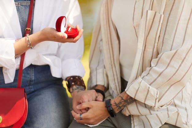 Close de lésbica segurando um anel e fazendo proposta para a namorada ao ar livre