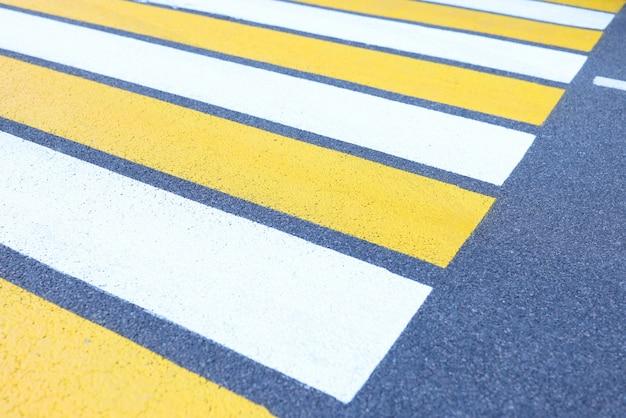 Close de listras brancas e amarelas em fundo cinza de asfalto