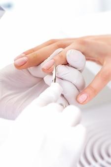 Close de manicure usando tesouras de manicure para remover cutículas de unhas femininas em salão de manicure