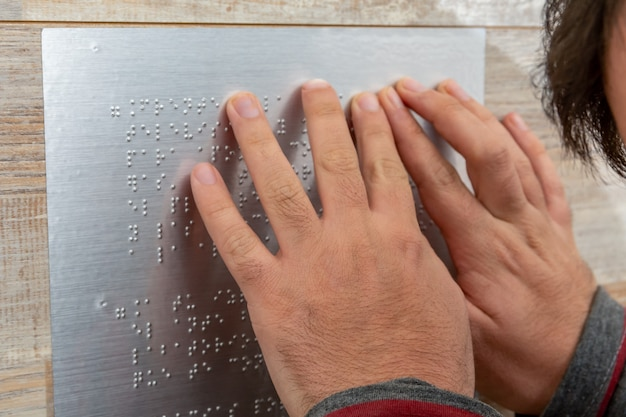 Close de mão masculina lendo texto em braille