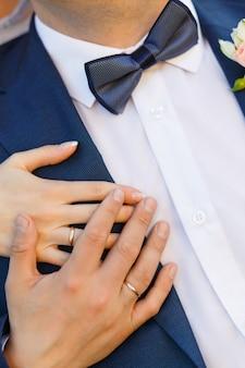 Close de mãos com anéis na cerimônia de casamento