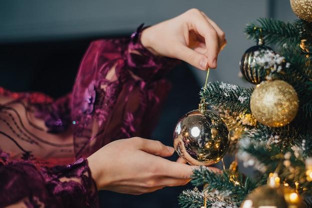 Close de mãos de mulher decorando a árvore de natal com bolas, chave baixa