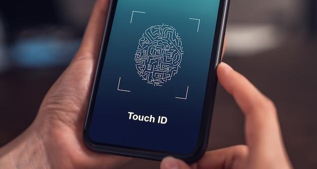 Close de mãos digitalizando a impressão digital no smartphone para desbloquear o celular na mesa