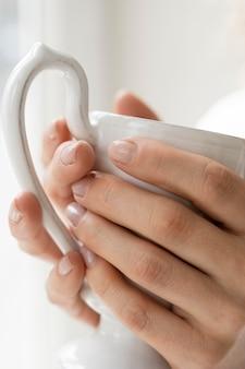 Close de mãos femininas com uma xícara de café