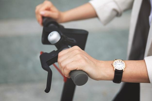 Close de mãos femininas e volante de scooter elétrico