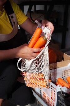 Close de mãos femininas empacotando cenouras