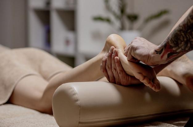 Close de mãos femininas fazendo massagem nos pés