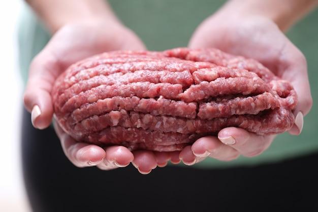 Close de mãos femininas segurando carne picada de carne bovina